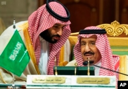 FILE - In this Dec. 9, 2018 file photo, released by the state-run Saudi Press Agency, Saudi Crown Prince Mohammed bin Salman, left, speaks to his father, King Salman, at a meeting of the Gulf Cooperation Council in Riyadh, Saudi Arabia.