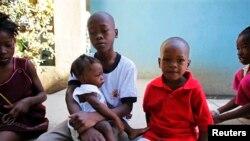 """Gesner, 13 zan , (goch a dwat) ak sè li Gloria, 1 an, ak frè li Gabriel, 3 zan , 3 viktim adopsyon ilisit nan vila NGO a, """"SOS Children's"""" nan Pòtoprens."""