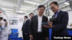 홍용표 한국 통일부 장관(왼쪽)이 10일 경기도 고양시 삼송테크노밸리에 입주한 개성공단 기업을 방문해 업체 관계자와 공장을 둘러보고 있다.