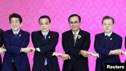 4일 태국 방콕에서 열린 아세안+3 정상회의에 앞서 기념촬영을 하기 위해 손을 엇갈려 잡은 각국 정상들. 왼쪽부터 아베 신조 일본 총리, 리커창 중국 총리, 쁘라윳 짠오차 태국 총리, 문재인 대통령.