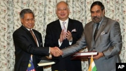 India's Commerce Minister Anand Sharma, right, shakes hand with Malaysia's International Trade and Industry Minister Mustapa Mohamed, left, as Malaysia's Prime Minister Najib Razak applauds during the signing ceremony of the Malaysia - India Comprehensive