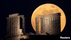 """The full moon, known as the """"Super Flower Moon"""" rises over the Temple of Poseidon in Cape Sounion, near Athens, Greece, May 26, 2021."""