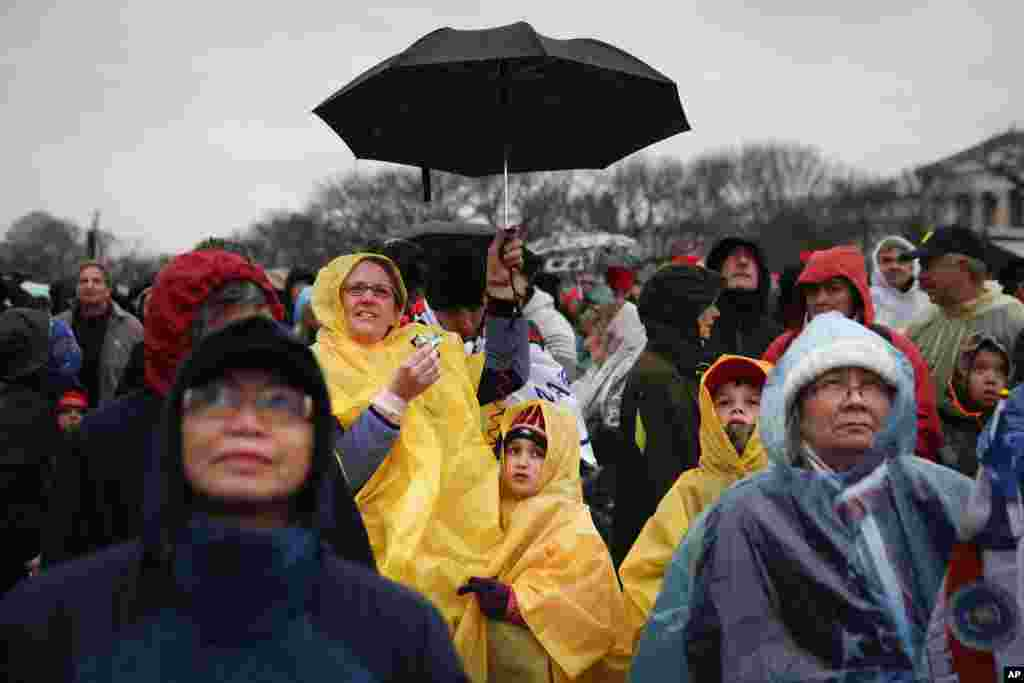 Spectators wait in the rain on the National Mall in Washington, Jan. 20, 2017, before the presidential inauguration of Donald Trump.