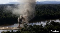 An illegal gold dredge is seen burning down at the banks of Uraricoera River during Brazil's environmental agency operation against illegal gold mining on indigenous land, in the heart of the Amazon rainforest, in Roraima state, Brazil, April 15, 2016.
