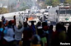 ພວກປະທ້ວງທີ່ສະໜັບສະໜຸນຝ່າຍຄ້ານພາກັນຮ້ອງໂຮຂຶ້ນເມື່ອເຫັນລົດທະຫານຖືກໄຟໄໝ້ ໃນຂະນະທີ່ໂຮມຊຸມນຸມກັນຕໍ່ຕ້ານ ປ. Maduro ຢູ່ນະຄອນຫລວງ Caracas, ວັນທີ 1, 2019