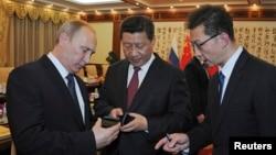 2014年11月9日俄羅斯總統普京在北京(左)向中國國家主席習近平(中)介紹俄羅斯生產的智慧手機-YotaPhone