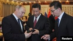 俄罗斯总统普京向中国国家主席习近平赠送手机。(2014年11月9日)
