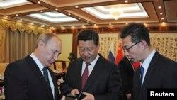 2014年11月9日俄羅斯總統普京在北京(左)向中國國家主席習近平(中)介紹俄羅斯生產的智能手機