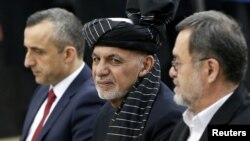 FILE - Afghanistan's President Ashraf Ghani, alongside his two vice president candidates, Amrullah Saleh, left, and Sarwar Danish, arrives to register as a candidate for the presidential election at Afghanistan's Independent Election Commission in Kabul, Jan. 20, 2019.