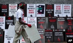 FILE - A protester walks past rows of placards during an anti-corruption demonstration in downtown Nairobi, Kenya, Dec. 1, 2015.