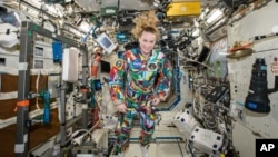 An undated handout photo from NASA shows astronaut Kate Rubins aboard the International Space Station wearing a hand-painted spacesuit decorated by childhood cancer patients at the University of Texas MD Anderson Cancer Center in Houston.