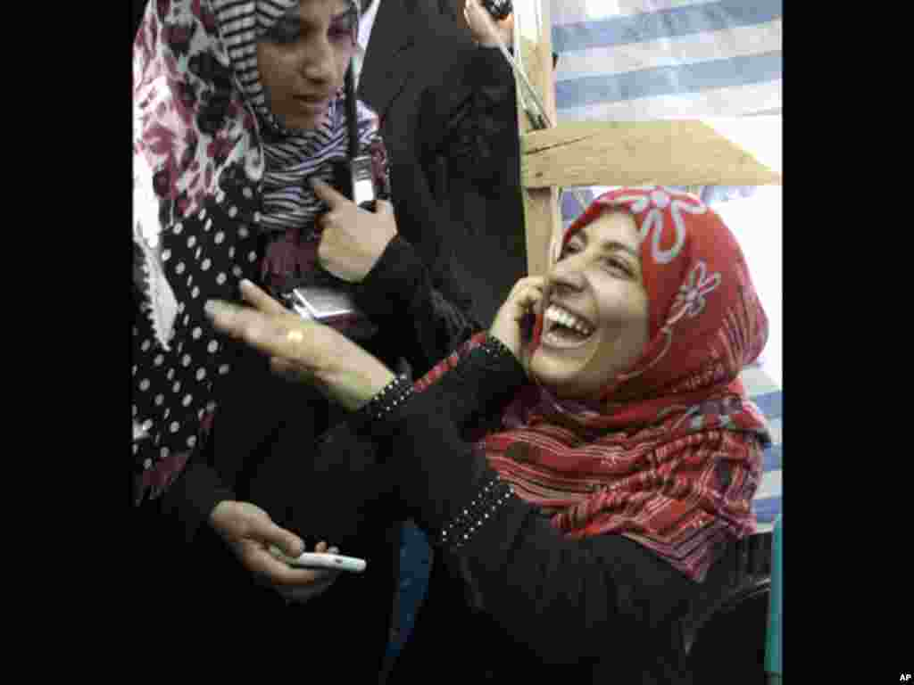 Yemeni activist Tawakkul Karman laughs as she speaks on the telephone after the announcement of the 2011 Nobel Peace Prize in Sanaa, Yemen, Friday, Oct. 7, 2011. The 2011 Nobel Peace Prize was awarded Friday to Liberian President Ellen Johnson Sirleaf, Li