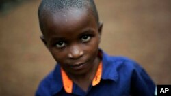 FILE - Shardrack Bahati, eight, sits outside his room at the En Avant Les Enfants INUKA center in Goma, Democratic Republic of Congo.