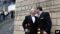 Terry Gilbert, left, kisses his husband Paul Beppler after wedding at Seattle City Hall, becoming among the first gay couples to legally wed in the state, December 9, 2012.