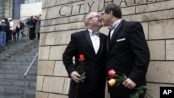 FILE - Terry Gilbert, left, kisses his husband Paul Beppler after wedding at Seattle City Hall, becoming among the first gay couples to legally wed in the state, December 9, 2012.