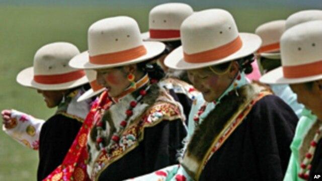 图为西藏那曲的藏民在绿地上起舞资料照