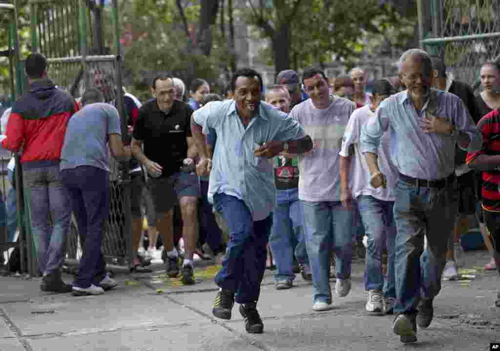 브라질 리우데자네이루의 한 학교에 마련된 대통령 선거 투표장으로 유권자들이 뛰어들어가고 있다.