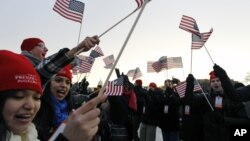 Spectators wave American flags on the National Mall in Washington, Jan. 21, 2013, before the start of President Barack Obama's ceremonial swearing-in ceremony during the 57th Presidential Inauguration.