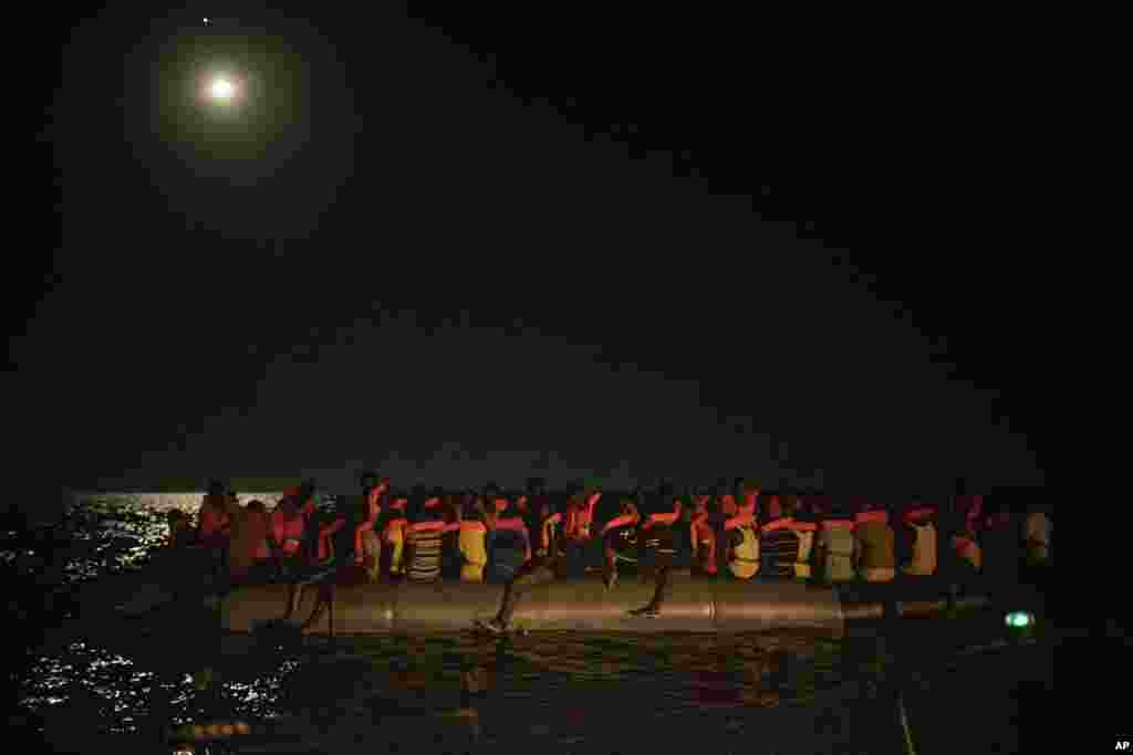 African migrants wait to be assisted by crew members of the Louise Michel and Astral rescue vessels, after being located sailing adrift on an overcrowded rubber boat, 70 miles southwest Malta, in the Central Mediterranean sea, Aug. 29, 2020.