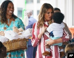 First lady Melania Trump holds a baby as she visits Greater Accra Regional Hospital in Accra, Ghana, Oct. 2, 2018.