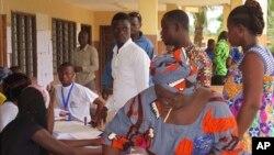 Une femme met son bulletin dans l'urne au bureau de vote de Seme Podji, au Bénin, le 6 mars 2016. (AP Photo/Virgile Ahissou)