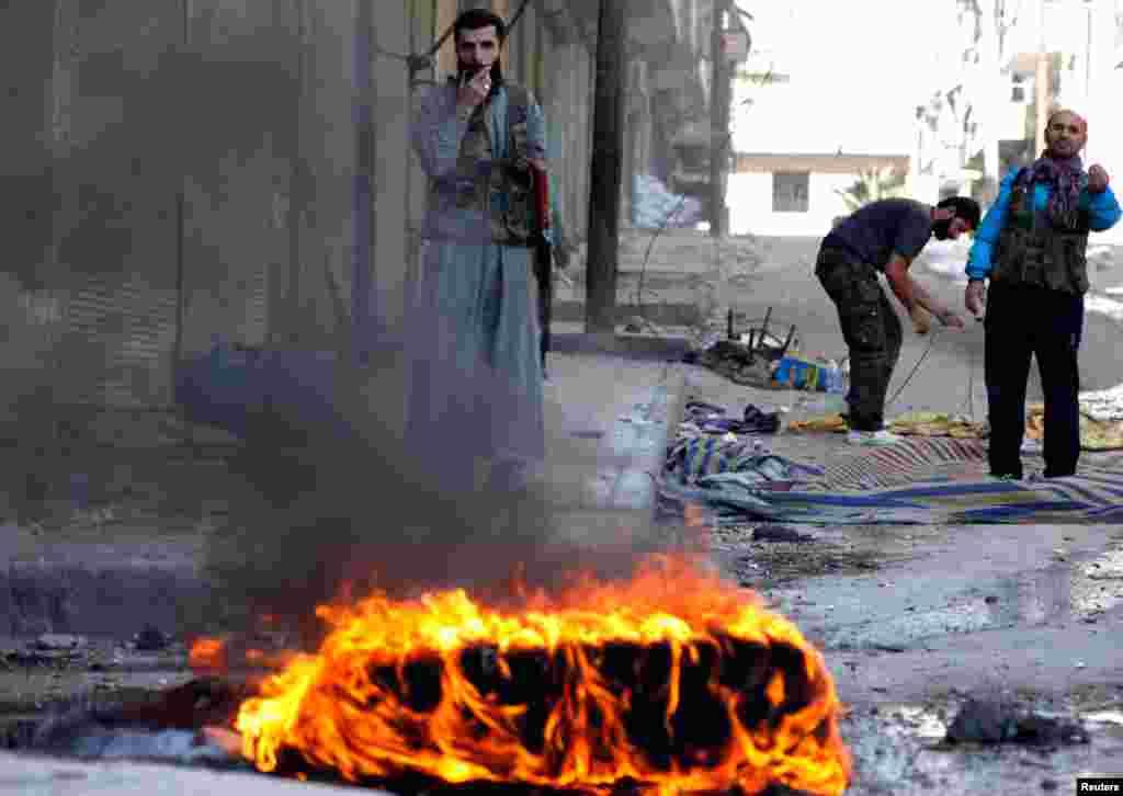 Binh sĩ thuộc Lực lượng Giải phóng Syria chiến đấu tại thị trấn Bustan Al-Basha trong thành phố Aleppo, ngày 15/10/2012