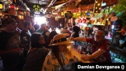 In this Wednesday, July 7, 2021, file photo, patrons enjoy cold tropical cocktails in the tiny interior of the Tiki-Ti bar as it reopens on Sunset Boulevard in Los Angeles.(AP Photo/Damian Dovarganes, File)