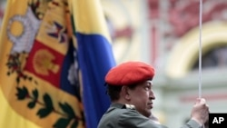 Venezuela's President Hugo Chavez hoists the national flag as he attends a ceremony in Caracas July 14, 2011