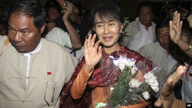 Myanmar opposition leader Aung San Suu Kyi, center, arrives at Rangoon International airport before departing for India in Rangoon, Burma Nov. 12, 2012.
