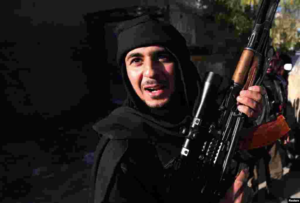 15일 다마스쿠스 인근 지역에서 총을 들고 있는 반군 병사.