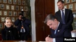 Penerima Hadiah Nobel Perdamaian, Presiden Kolombia Juan Manuel Santos menandatangani surat di kantor Institut Nobel di Oslo, Norwegia, 9 Desember 2016, disaksikan oleh ibu negara Norwegia, Maria Clemencia Rodriguez dan Direktur Institut Nobel, Olav Njoelstad. (NTB Scanpix/Heiko Junge via REUTERS).