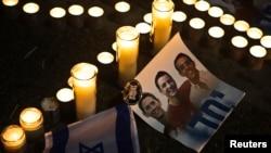 Ảnh của 3 thiếu niên Israel bị bắt cóc và sát hại đặt cạnh những ngọn nến tưởng niệm, tại Quảng trường Rabin ở Tel Aviv, 30/6/14