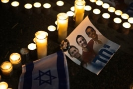 Candles placed next to a picture of three Israeli teenagers who were abducted and killed, in Tel Aviv's Rabin Square, June 30, 2014.
