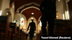 Anggota pasukan khusus polisi memegang senjata saat berjalan di dalam Katedral Makassar menjelang misa Natal, di Sulawesi Selatan, 24 Desember 2011. (Foto: REUTERS/Yusuf Ahmad)