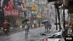 Warga di Pondicherry, India tenggara berjalan di antara guyuran hujan dan angin kencang, sementara papan iklan di jalan berantakan akibat topan Thane (30/12).