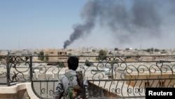 FILE - Seorang pejuang Kurdi dari unit People's protections melihat asap yang membumbung akibat serangan udara pasukan koalisi di Raqqa, Suriah. (16 Juni 2017)
