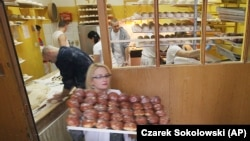 A worker carrying trays of paczki at a pastry shop for Fat Thursday in central Warsaw, Poland, Thursday, Feb. 4, 2016.