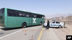Police inspect an Israeli bus involved in a shooting attack along the border between Israel and Egypt in southern Israel, August 18, 2011