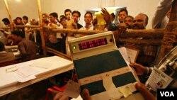 Seorang petugas pemilu menggunakan alat elektronik untuk menghitung perolehan suara di Lucknow, India (6/3).