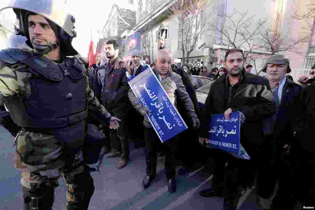 An Iranian riot policeman stands guard as protesters hold street signs with the name of Shi'ite cleric Sheikh Nimr al-Nimr during a demonstration condemning his execution in Saudi Arabia, outside the Saudi Arabian Embassy, in Tehran, January, 3, 2016.