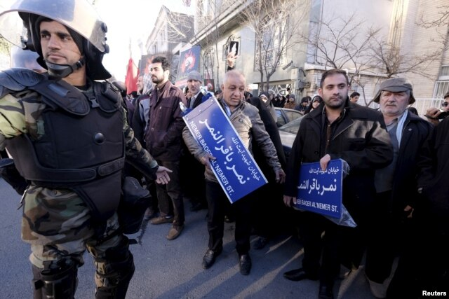 An Iranian riot policeman stands guard as protesters hold street signs with the name of Shi'ite cleric Sheikh Nimr al-Nimr during a demonstration condemning his execution in Saudi Arabia, outside the Saudi Arabian Embassy, in Tehran, Jan., 3, 2016.