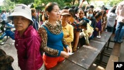 Cambodian villagers line up to cast their vote in the country's national election at a polling station at Chak Angre Leu pagoda, in Phnom Penh, Cambodia, Sunday, July 28, 2013.