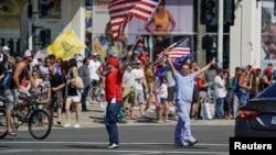 Warga AS keluar rumah dan menyerukan pembukaan kembali negara bagian California dalam aksi unjuk rasa di Huntington Beach, California Jumat (1/5).