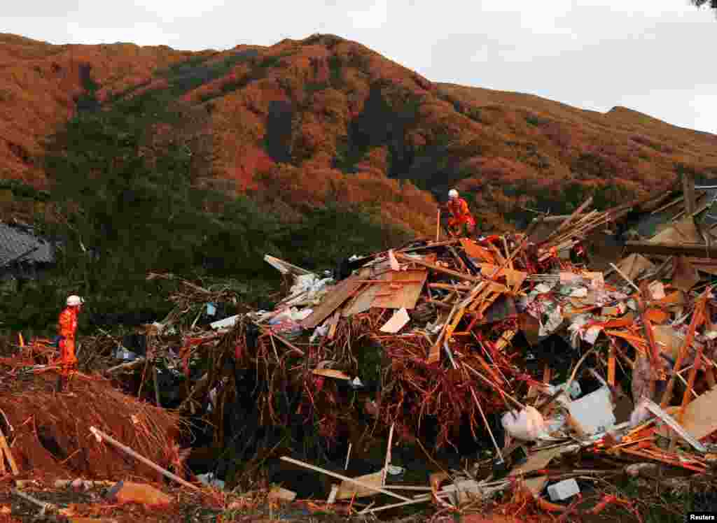 Firefighters search for missing people among collapsed houses following a landslide caused by Typhoon Wipha on Izu Oshima island, south of Tokyo, in this photo taken by Kyodo, Oct. 16, 2013.