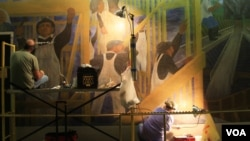 Art conservators at work on the historic mural at VOA