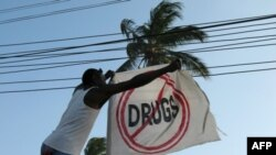 A former addict straightens a flag outside a sober house in Zanzibar