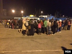 Refugees crowd around bus drivers in Athens that promise to take them directly to the Macedonia border, Athens, Sept. 2015. (H.Murdock/VOA)