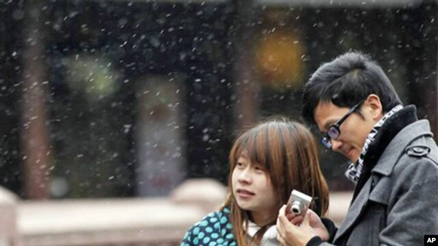 A couple visit snowy Yuyan Garden, one of the most popular tourist destinations in town, in Shanghai, China, Dec. 15, 2010.