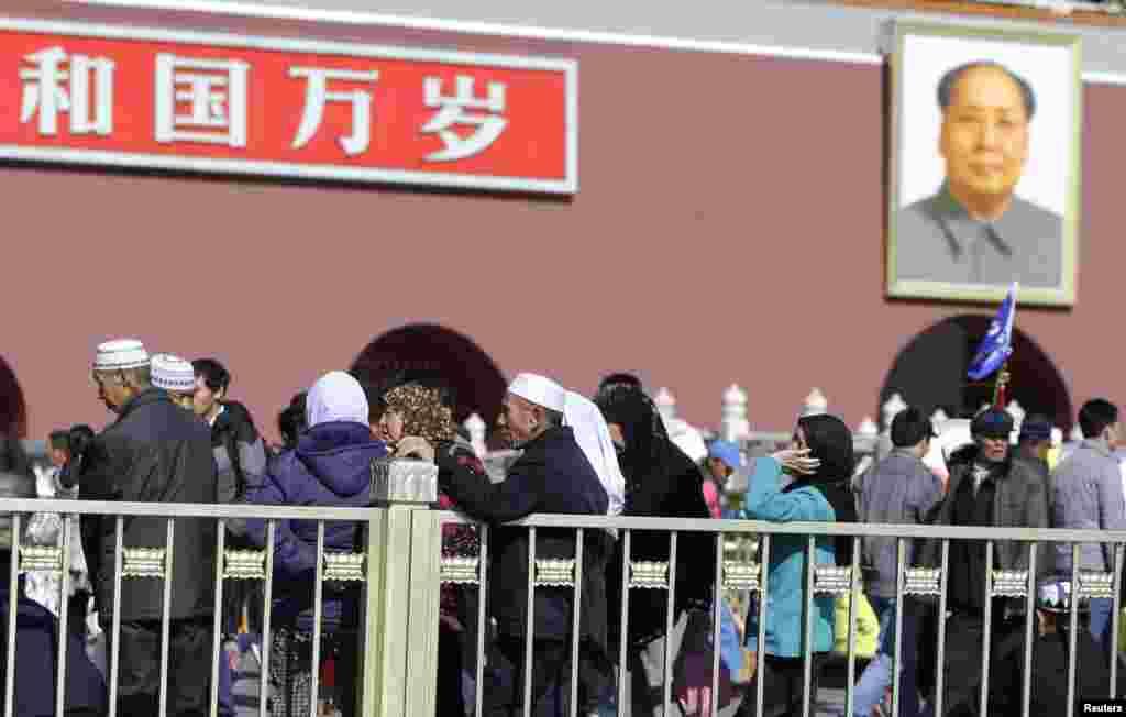 گردشگران در مقابل پرتره مائو تسه تونگ در میدان تیانانمن - پلیس در جستجوی دو فرد مظنون از استان سین کیانگ است که آنها را مسئول تصادف مرگبار در میدان تیانانمن می داند. ۳۱ اکتبر ۲۰۱۳