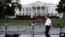 Seorang petugas Secret Service bersama anjing pelacak melakukan patroli di luar komplek Gedung Putih, Senin (22/9).